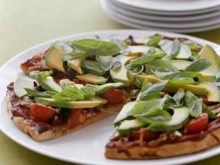 Avocado-Pizza mit Tomaten und Basilikum