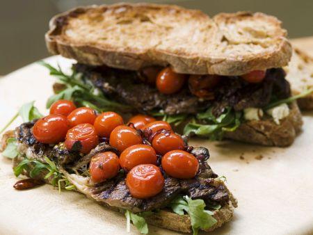 Brote mit Steak, geschmorten Tomaten und Rucola
