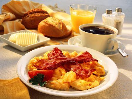 Frühstück mit Rührei und Speck, Kaffee, Orangensaft, Brötchen
