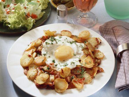 Gebratene Kartoffeln mit Spiegelei und grünem Salat