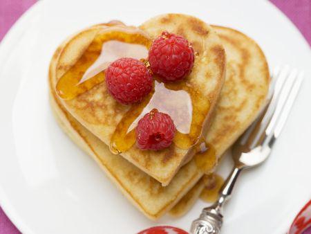 Kleine Herz-Pfannkuchen mit Himbeeren und Ahornsirup