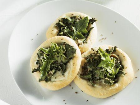 Kleine Pizzen mit Löwenzahn, Blauschimmelkäse und Kümmel