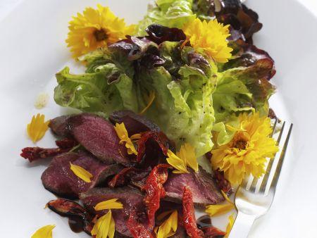 Lammfleisch mit grünem Salat und Essblüten