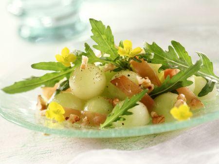 Melonensalat mit Rucola, Lachsschinken, Nüssen und essbaren Blüten