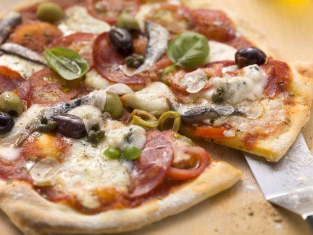 Pizza mit Salami, Gorgonzola, Anchovis und Oliven