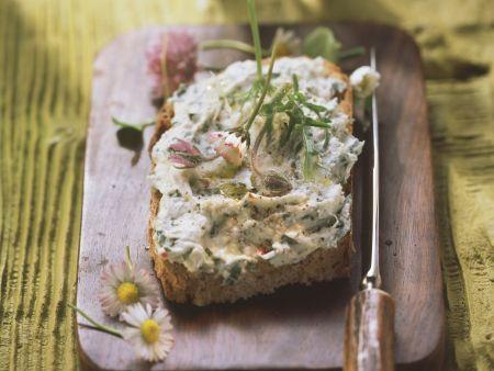 Rustikales Brot mit Kräuterbutter und Gänseblümchen