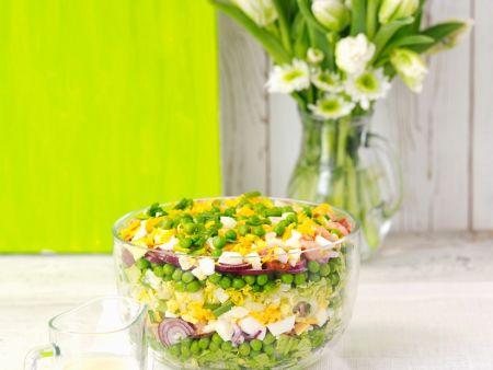 Schichtsalat mit Zwiebeln, Ei, Speck, Erbsen und Käse