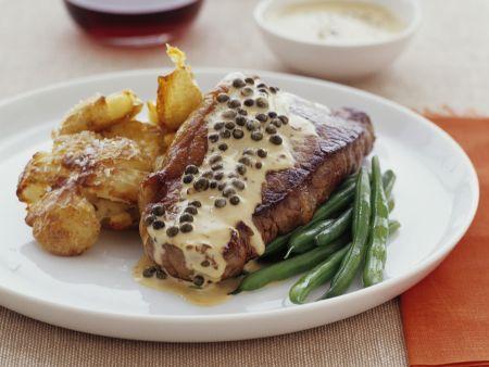 Steak mit Pfeffersoße, Bratkartoffeln und Bohnen