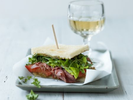 Toast mit Tomatensauce, würzigem geräuchertem Fleisch (Pastrami) und Salatblättern