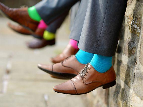 Männer-Bein in Business-Hosen und bunten Socken