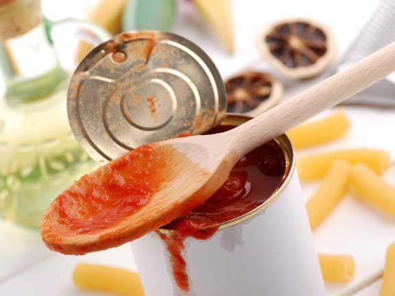 Eine geöffnete Dose Tomaten mit einem Kochlöffel