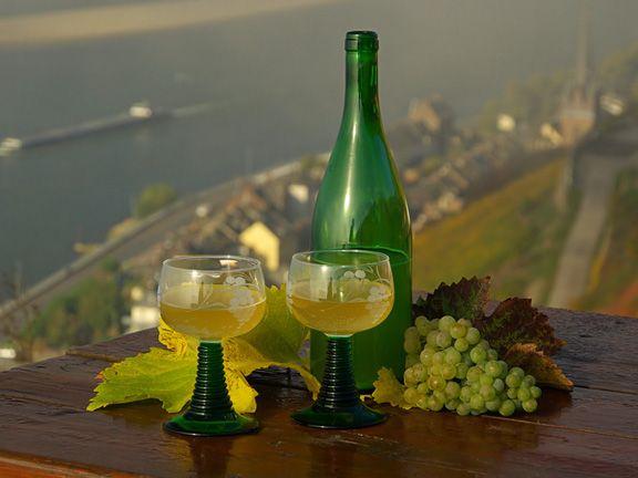 Eine Flasche Federweißer mit zwei Römergläsern vor der Moselschleife fotografiert