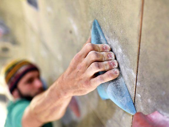 Mann beim Bouldern in einer Kletterhalle