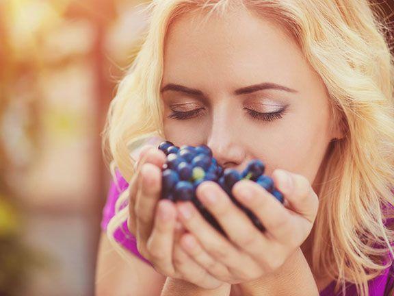 Frau riecht an Weintrauben