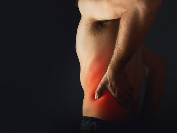 Mann hält sich den schmerzenden unteren Rücken
