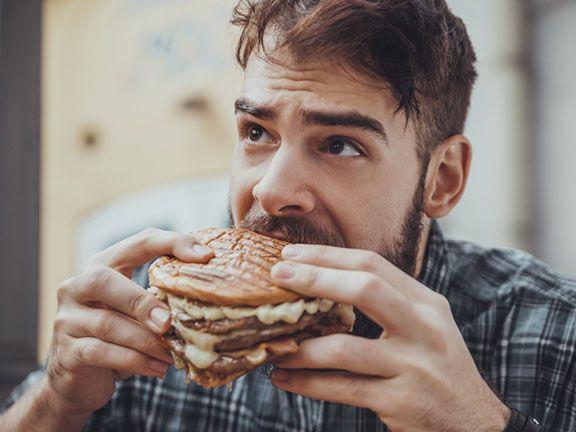 Mann isst Burger