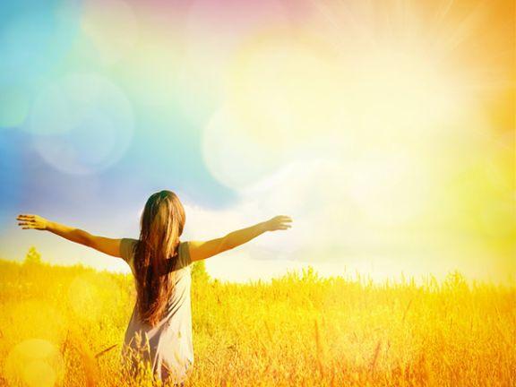 Frau steht auf einem Feld und genießt