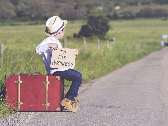 """Kleiner Junge mit Koffer und Schild """"Way to the Happiness"""" sitzt an einer Landstraße"""