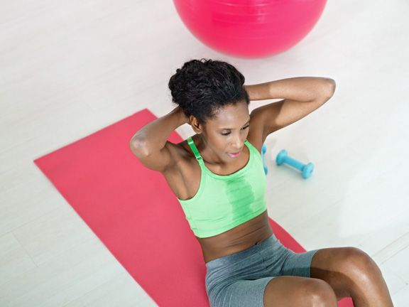 Dunkelhäutige Frau macht Crunches auf einer Fitnessmatte