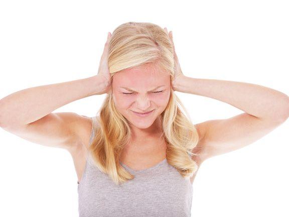 Junge blonde Frau hält sich beide Ohren zu