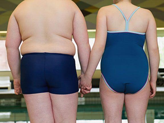 Übergewichtiger Junge und übergewichtiges Mädchen im Schwimmbad