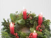Adventskranz mit vier brennenden Kerzen Rezept