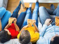 Familie sitzt auf dem Sofa, sieht fern und isst Pizza aus der Hand