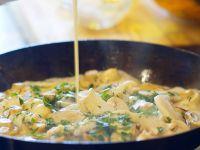 Sahne in eine Gorgonzola-Pilz-Sauce giessen