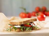 Sandwich aus Vollkorntoast mit Mozzarella, Tomate und Rucola Rezept