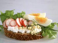 Scheibe Vollkornbrot mit Hüttenkäse, Radieschen, Sprossen und Ei Rezept