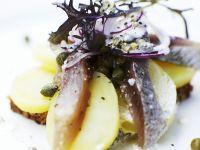 Schwarzbrot mit Belag aus Kartoffeln, Sardellen, Kapern und Zwiebeln Rezept