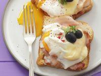 Toast mit Schinken, verlorenem Ei, Oliven und Käse