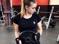 Frau im Fitnessstudio mit Hantelscheibe