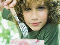 Junge mit lockigen Haaren pikst mit einer Gabel in ein Stück Kuchen