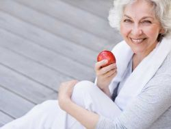 Abnehmen ab 50: Seniorin mit Apfel