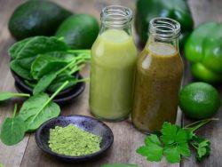 Zwei Flaschen mit grünem Smoothie neben Blättern von jungem Spinat