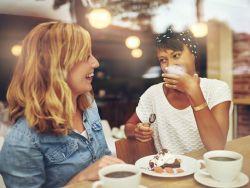 Zwei Frauen trinken Kaffee und essen Kuchen