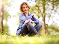 Frau in den besten jahren sitzt im Wald auf einer Wiese