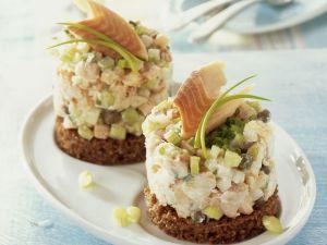 Forellen-Tatar mit Gurke und Lauchzwiebeln auf Pumpernickel Rezept