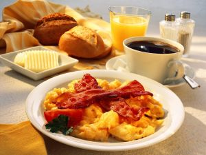 Frühstück mit Rührei und Speck, Kaffee, Orangensaft, Brötchen Rezept
