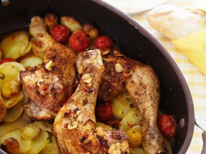 Gebackene Hähnchenkeulen auf Kartoffeln und Trauben Rezept