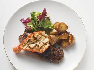 Gegrilltes Steak mit Garnelen und gebratenen Kartoffeln Rezept