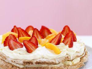 Haselnuss-Baisertorte mit Erdbeeren, Pfirsich und Schlagsahne Rezept