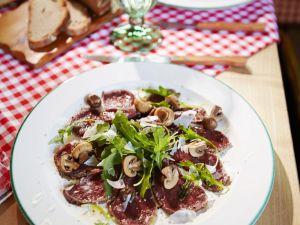 Hirschcarpaccio mit Rucola, Parmesan und Champignons Rezept