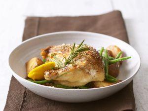 Ofengebackene Hähnchenkeulen mit Kartoffeln Rezept