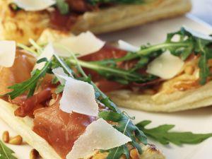 Pizzaschitten mit rohem Schinken, Rauke und Parmesan Rezept