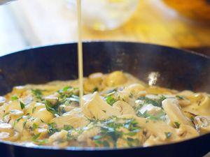 Sahne in eine Gorgonzola-Pilz-Sauce giessen Rezept