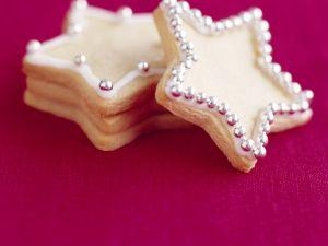 Sternförmige Plätzchen mit Silberperlen vor lila Hintergrund Rezept