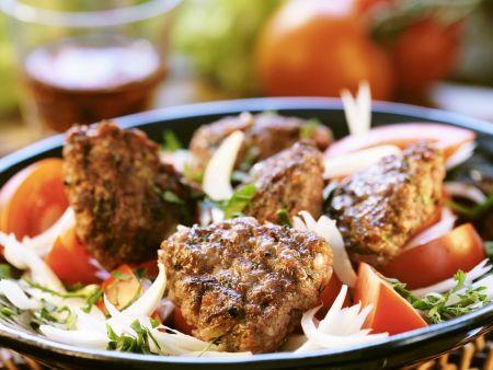 Buletten auf Zwiebel-Tomaten-Salat