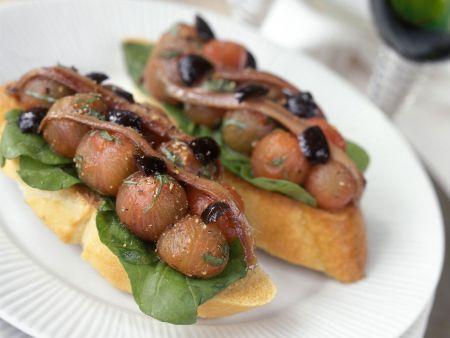 Crostini mit geschälten Tomaten, Oliven und Sardinen